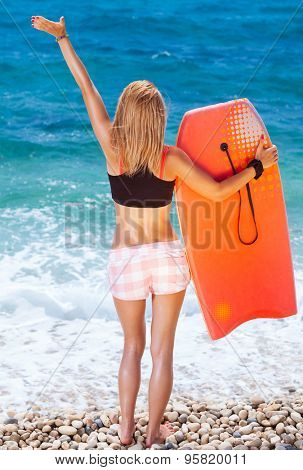 Sportive woman on the beach, slim girl standing back side and enjoying beautiful sea view with surfboard in hand and another hand raised up, enjoying active summer vacation