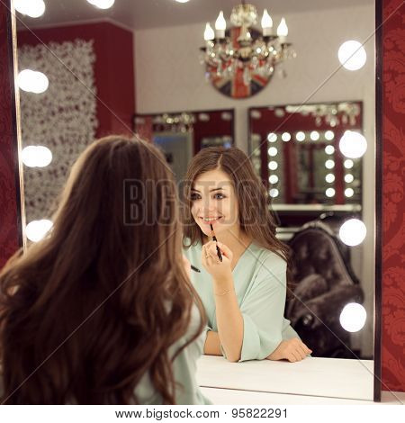 Young beautiful woman with make up and reflection in dressing room