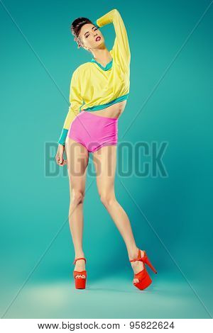 Glamorous fashion model alluring in vivid colourful clothes and high heels platform shoes. Bright fashion. Full length portrait. Studio shot.