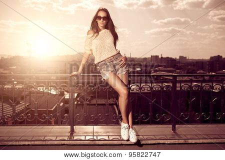 Beautiful brunette young woman wearing sunglasses, shorts, white top posing above sunset city background. Hot summer.