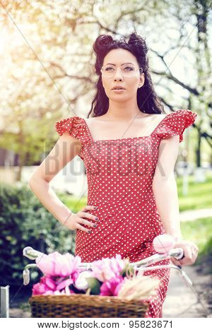 sexy woman wearing vintage dress. pin-up sitting on bicycle with some colorful flowers in the basket