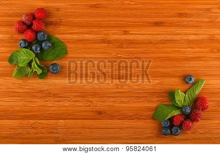 Cutting Board With Blueberries, Raspberries And Mint Leaves In Corners