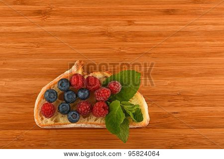 Cutting Board With Sandwich Of Blueberries And Raspberries On Bread