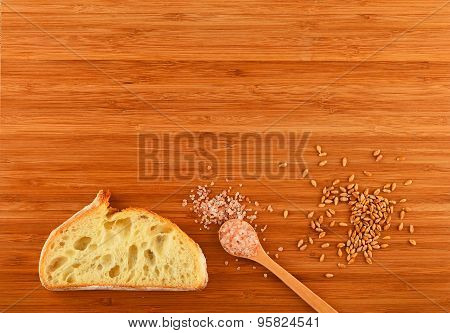 Cutting Board With Spoon Of Himalayan  Salt, Wheat Grains And Bread