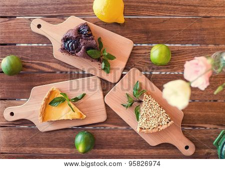 Pieces of nut cake, brownie and cheesecake decorated with mint, lemon, lime on wooden table. top vie