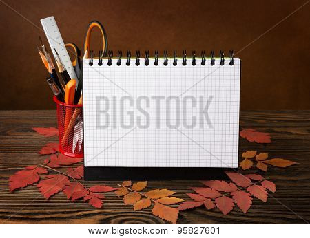 School equipment with pencils,  notebook  and autumn leaves on wooden table . Back to school concept.