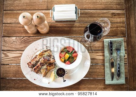 Grilled pork ribs with salad, lemon, sauce and the glass of red wine. Top view