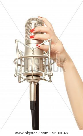 Woman's Hand With Red Nails Holding Microphone