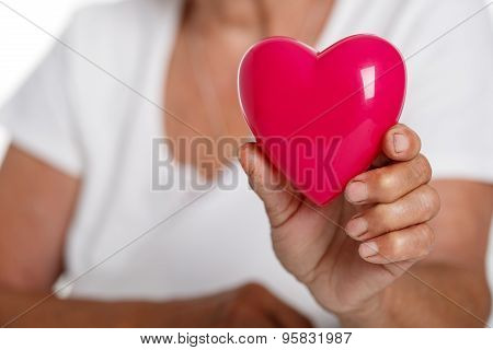 Elder Woman Holding Red Toy Heart In Front Of Her Chest