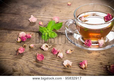 Cup of green tea with mint and dried roses