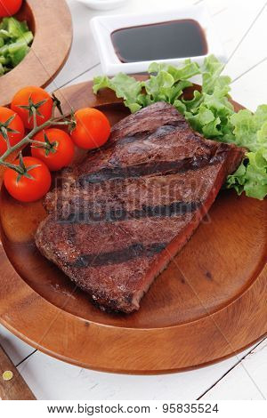 lunch of fresh rich juicy grilled beef meat steak fillet with marks on wooden plate over white table served with vegetable salad and cutlery, new york styled cuisine