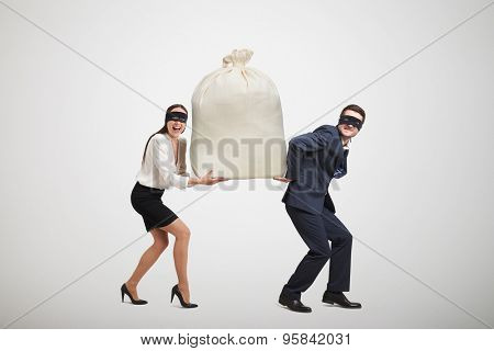 laughing woman and man in formal wear and black mask on the eyes holding big bag and looking at camera. isolated on light grey background