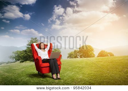 relaxed woman with closed eyes sitting on the red chair with laptop on green meadow over hill and blue sky