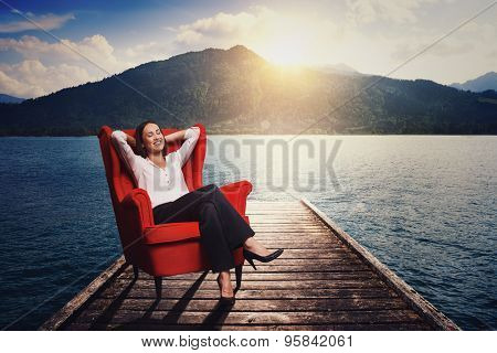 smiley woman resting and dreaming on the red chair on wood moorage over beautiful landscape
