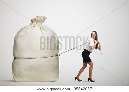 happy woman in formal wear pulling big bag over light grey background