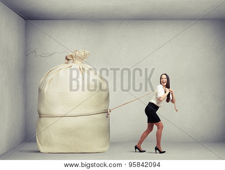 happy woman in formal wear pulling big bag in grey concrete room