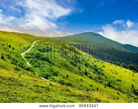 Road Through Hillside In High Mountains At Sunrise