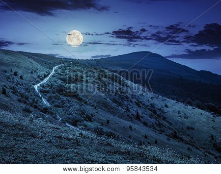 Road Through Hillside In High Mountains At Night