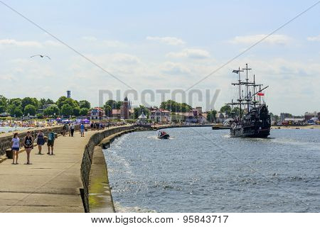 USTKA - JULY 07: Tourists enjoy the sunny weather and walking on the harbor breakwater on 7 July 2015 in Ustka, Poland.
