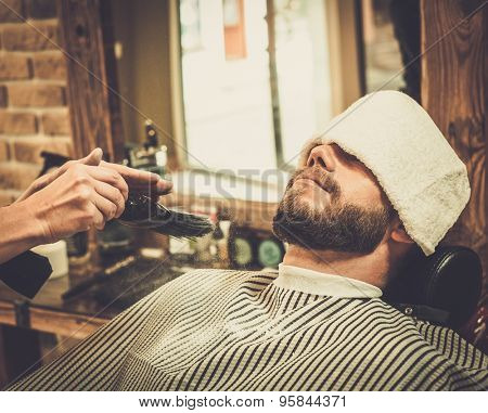 Hairstylist applying  beard powder in barber shop