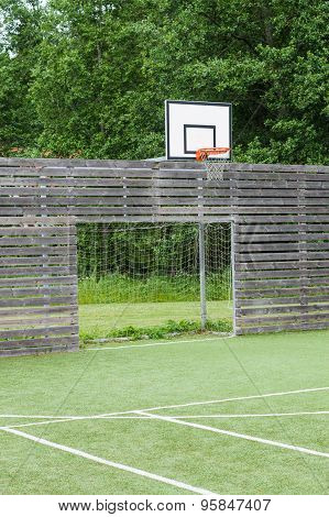Soccer Goal And Basketball Hoop On Outdoor Playground With Synthetic Field