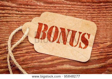 bonus sign a paper price tag against rustic red painted barn wood - shopping concept