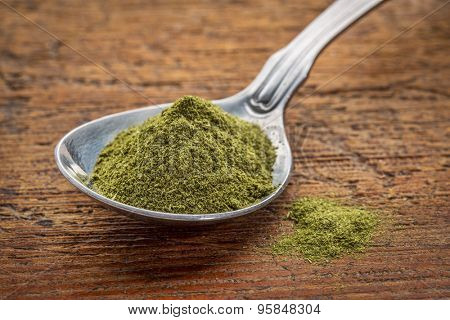 green freeze-dried organic wheat grass powder, nutritional supplement on a tablespoon against rustic wood