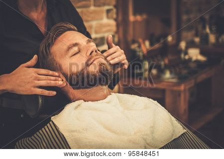 Hairstylist applying after shaving lotion in barber shop