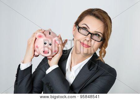 Beautiful Smiling Businesswoman Shaking Piggy Bank