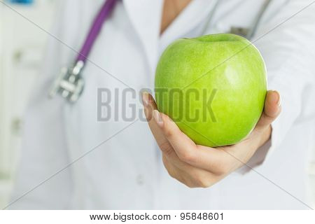 Female Doctor's Hand Offering Fresh Green Apple