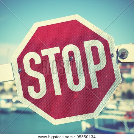 Stop traffic sign on the barrier. Retro style filtred image