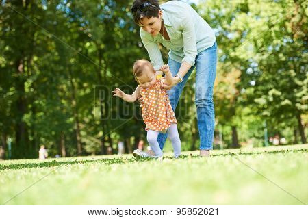 happy mother and baby child in park making first steps .  Walking and hugging.