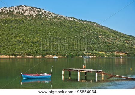 Small boat near old rusty dock at sunny morning in Porto Koufo
