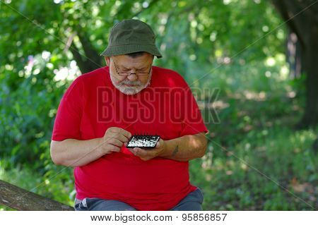 Bearded man playing mini-chess with himself in a park