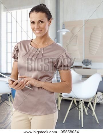 Happy businesswoman holding tablet, smiling, looking at camera.