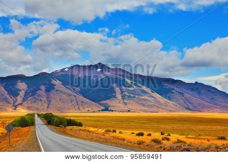 Steppes of Patagonia. Smooth asphalt road passes between the yellow plain to the distant mountains