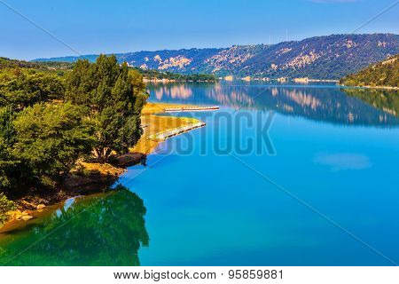 Smooth emerald green water of Lake Sainte-Croix-du-Verdon reflects the sky and wooded shore. Mountain canyon Verdon in the French Alps