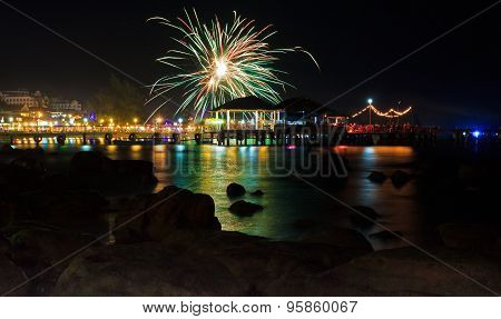 Colorful Fireworks At Pier In Sihanoukville, Cambodia With Reflection In The Water And Silhouettes