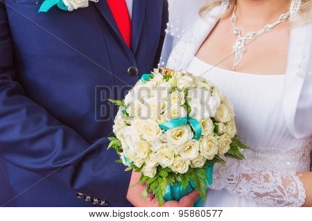 small bridal bouquet in hands and rings on it