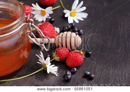 Honey glass,wooden dipper,berries on dark background