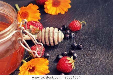 Honey glass,wooden dipper,berries, calendula on dark background