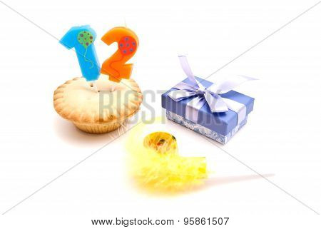 Cupcake With Twelve Years Birthday Candle, Gift And Whistle On White