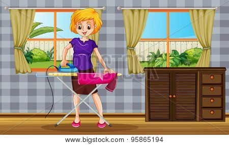 Woman standing and ironing a shirt in a room with garden view behind