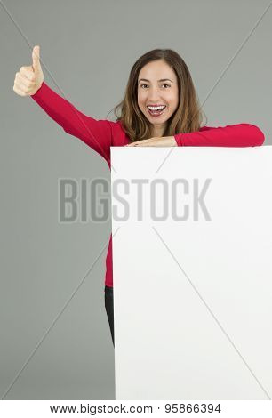 Excited Woman Showing Advertising Board And Giving Thumbs Up