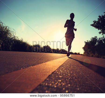 young fitness woman running on sunrise seaside trail