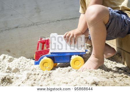 Young Boy Playing With His Plastic Truck Toy On White Sand