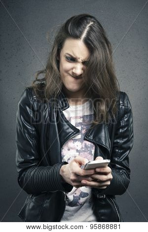 Angry Young Girl Looking At Phone With Disgusting Emotion