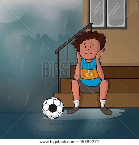 Cute little sad boy sitting at stairs with soccer ball in a rainy day for Mossoon Season concept.