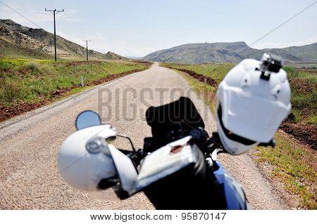 Two Helmets On A Motorcycle Handlebar