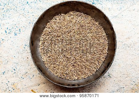 Closeup view of Raw Cumin seeds kept on an iron bowl